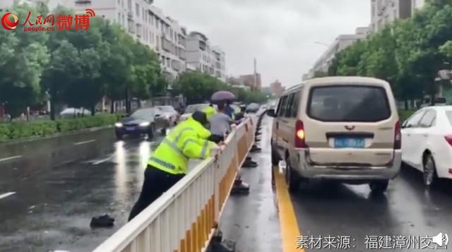 这一幕让人心疼!台风天执勤交警扶护栏被压倒,网友:看着都痛